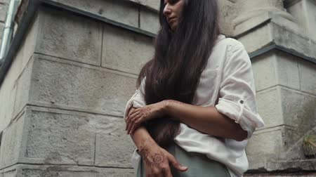 かぎ針編み : Close up shot of attractive model with a beautiful henna art on her hands. Woman in stylish clothes standing by the building.