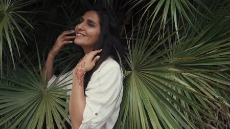 bescheiden : a young and long-haired woman is standing in palm groves, the lady touches herself with her hands with a happy expression, her fingers have a tattoo of henna, called mehendi
