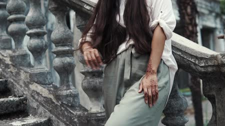 かぎ針編み : Charming brunette woman is posing on outside staircase of ancient building on vacation. Woman in stylish clothes and with mehndi on hands.