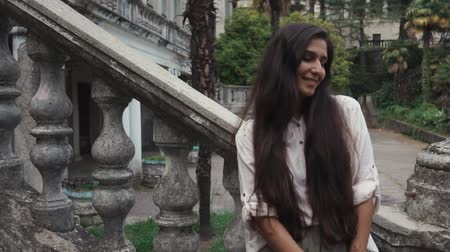 bescheiden : a young woman with dark long hair is standing near the stairs with a stone frame, the lady has tattooed mehendi on her hands, she is looking away while in the park Stockvideo