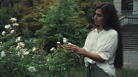 szag : Portrait of charming woman with long brunette hair smelling exotic flowers in the garden. Spending time outside on vacation. Sweet smell.