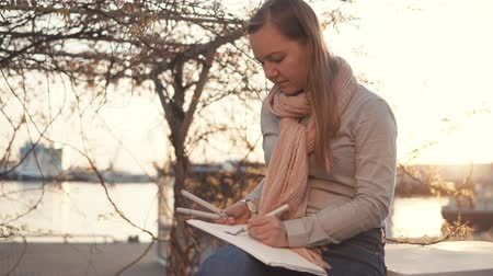 skillful : Young blonde girl is sketching in sketchbook during walking in park. She is holding paper on knees and using felt pens for drawing
