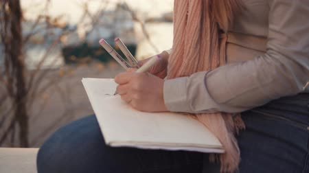 písanka : Young talented artist girl is sketching pictures outdoors. She is relaxing in park and inspiring for drawing