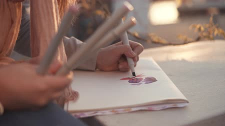 szakképzett : Young painter woman is sketching in a park in evening. She is drawing using multicolor professional felt pens, close-up