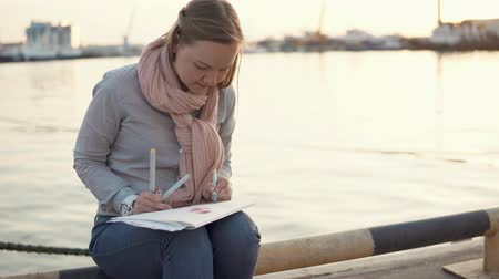 obra prima : Blonde girl is artist is sketching outside. She is sitting on quay of sea in evening and drawing in a sketchbook