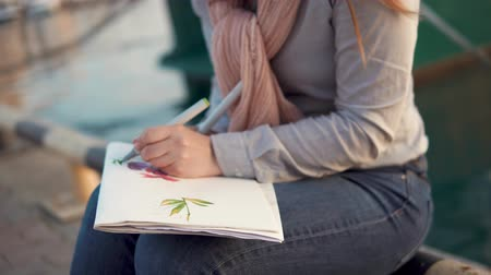 skillful : Girl is painting picture with floral patterns. She is using markers and sitting on embankment in tranquil spring evening