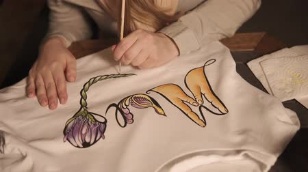 dyes : Artist is painting shirt by acrylic dyes. She is covering fabric by beautiful floral ornament, handmade of clothing
