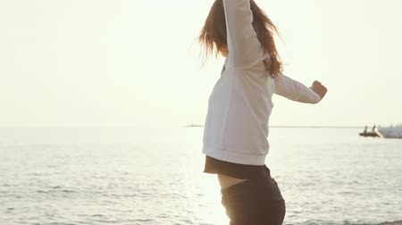 descuidado : Young brunette woman is rejoicing and spinning around herself on beach in sunset time. She is having fun alone, moving hands against the sun