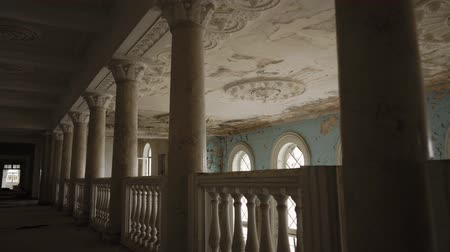 zanedbaný : Moving shot in old dilapidated building. Showing empty long tunnel, columns and ceiling with peeling paint