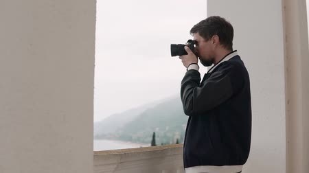 objektív : Man is holding modern camera in hands and looking through objective lens in distance. He is taking pictures of calm landscapes in cloudy weather from building Stock mozgókép