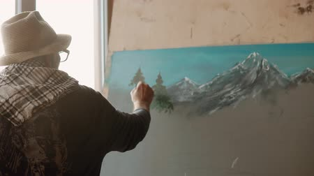 galeria : Inspired old painter is drawing spruces on a picture with mountains landscape. He is standing back to camera, and using artistic brush Stock Footage