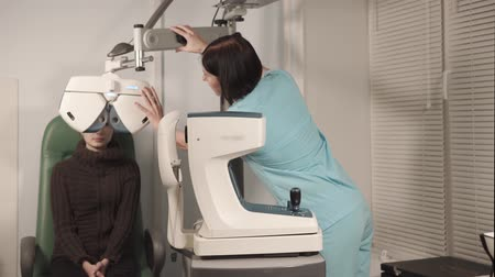 refractive : the doctor the ophthalmologist adjusts or adjusts the device orropotor for measurement of a refractive error of an eye, the patient is in a polyclinic Stock Footage