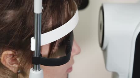 intraocular : Woman is in a doctor office in ophthalmological clinic. She is wearing tape on head and looking in an apparatus for examining vision, close-up