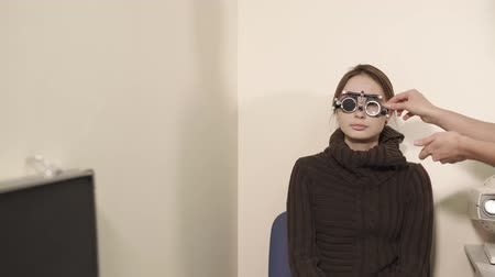 fixação : a portrait of a teenager who checks the vision with the help of visionimetry, an ophthalmologist dressed on a lady special glasses, the doctor changes lenses to determine visual acuity