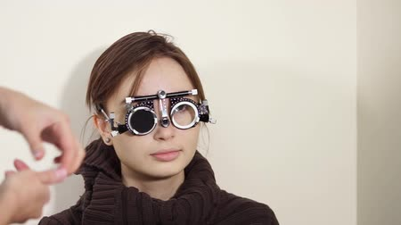 лучше : Close up shot of girl visiting oculist for measuring eyesight. Wearing eye testing glasses. Choosing better lenses for each eye.