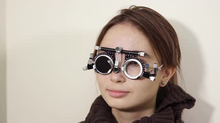 düzeltme : a portrait of a teenager who checks the vision with the help of visionimetry, the girl wears special glasses in which the lenses are gradually changed to determine visual acuity