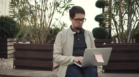 rövidszőrű : Portrait of a young and ambitious freelancer with a laptop sitting in a park. Man is sitting on the bench and working outside. Handsome guy.