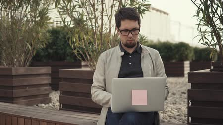 rövidszőrű : Smart and confident guy working outside in a park on a laptop. Businessman sitting on a bench and doing business. Freelancer working.