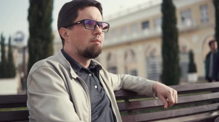 строгий : Close up portrait of a stylish man spending quiet day outside enjoying the weather. Man in glasses sightseeing. Sitting on bench in a park.