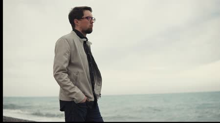 somente para adultos : Portrait of a confident handsome man standing alone on the beach. Cold weather and strong wind on the beach. Bad weather. Enjoying the view. Stock Footage