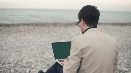 oceanos : Inspired freelancer sitting on the beach alone with a laptop and doing his job. Man spending time on the shore and writitng. Quiet place for work outside.