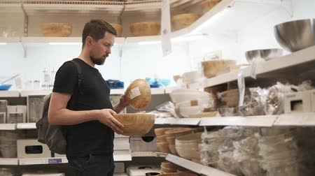 prodávat : Adult man is choosing new bowls for the kitchen in supermarket. Shopping for kitchen stuff. Products for home. Dinnerware. Dostupné videozáznamy