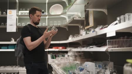 духи : Adult man is choosing two small glass in shop. He is holding them in hands and looking on racks, in big supermarket
