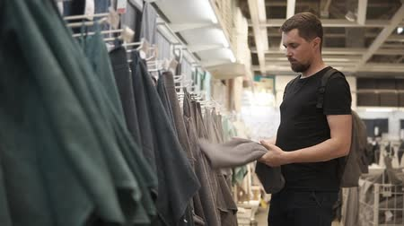 абсорбент : Young man is touching towels in a shop hall. He is choosing textiles for home and family, looking and selecting best goods