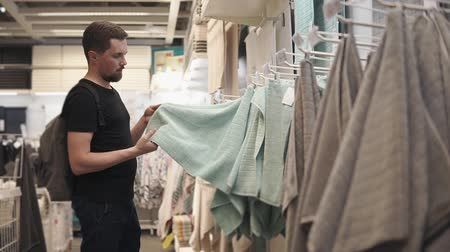 higiênico : Male shopper is touching soft towel in sale area in big shop. He is doing shopping goods for home, choosing independently Stock Footage