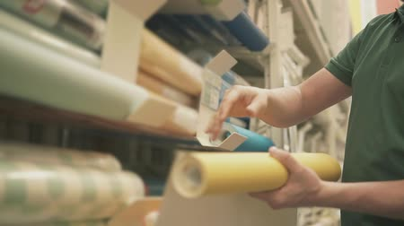 selecionando : Close up shot of a man rolling out yellow wallpaper while holding it in a store. Checks the quality and texture of wallpaper. Stock Footage