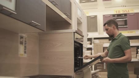 construído : Male shopper is opening door of new modern oven in store. He is planning to buy furniture and home appliances, trying and checking