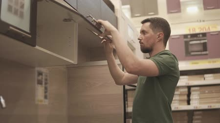 construído : Visitor is checking quality of kitchen furniture in a store. Man is opening door and looking inside, noticing scratches on handle Stock Footage
