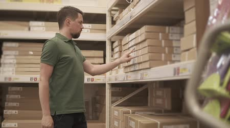 self storage : Visitor man is inspecting price tags on shelves with goods. He reading information and looking for a box inside, in storage of big store Stock Footage