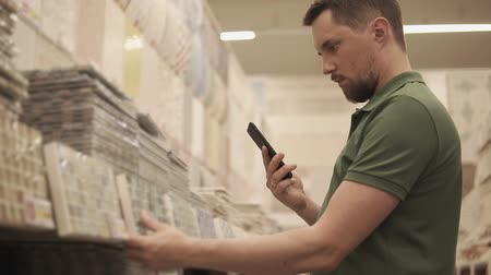 catalog : Close up shot of a man taking a photos of a tile in a building store. Male consumer buys new tile in the house. Laying tile in flat. Stock Footage