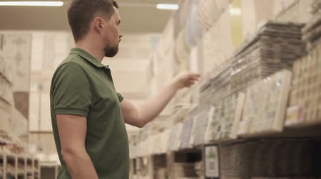 příklad : Shopper is comparing different color wall ceramic tiles in a sales area in big store. He is standing near shelf and taking samples, looking on them