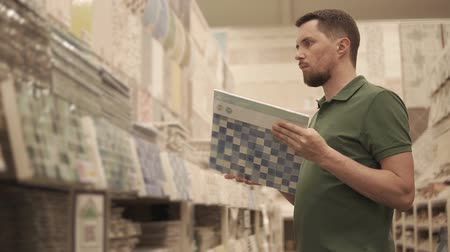 ceramika : Shopper man is standing in trading area of huge retail shop with building materials. He is looking samples of ceramic tiles for walls