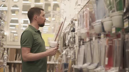 titular : Male visitor of big shop is holding in hands pack with toilet brush. He is deciding to buy items for bathroom and washroom Stock Footage