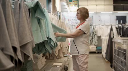 абсорбент : Female shopper is touching soft cloth in trading area in big store. She is doing shopping goods for home, choosing regardless