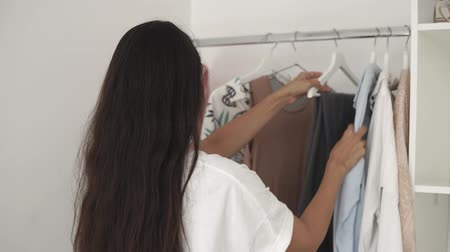 kledingstuk : Young woman is deciding what to wear in morning. She is taking clothes from rack and trying on her body