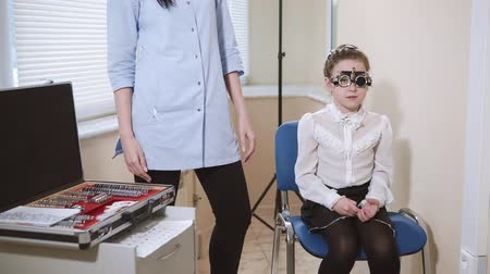 inspecting : Cute small girlie is sitting on a chair in ophthalmologist office. Doctor is filling lenses in frame and girl is reading symbols Stock Footage
