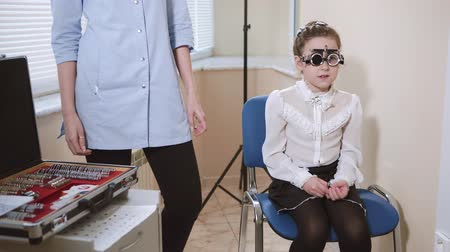 painless : a portrait of a teenager who checks the vision with the help of visionimetry, an ophthalmologist stands next to her, the girl checks the clarity of vision with the help of a vidiometry