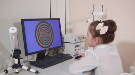 clareza : a portrait of a child who looks at a computer that is in the office of a pediatric ophthalmologist, the child determines the level of color perception for further treatment