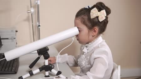 yarık : Little girl is looking into white pipe of modern ophthalmological equipment. She is sitting on a chair during medical examining Stok Video