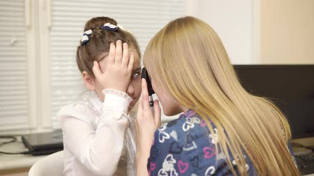 examination room : Blonde female oculist is examining eye of child girl. She is using ophthalmoscope for examining a fundus sections