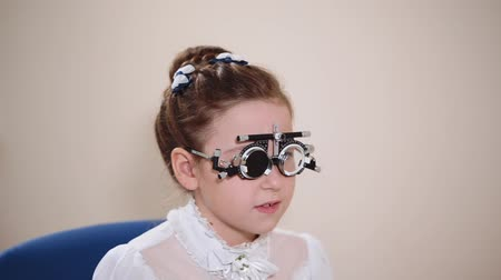 clareza : a portrait of a teenager who checks the eyes of an ophthalmologist, the physician uses a visionometry, an ophthalmologist uses special glasses to adjust the clarity Stock Footage