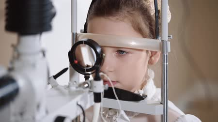 lom světla : Close up shot of a girl sitting on eye biomicroscopy. She is getting her eye examined on a slit lamp. Dostupné videozáznamy