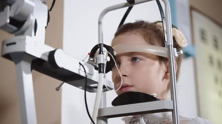 yarık : Face of schoolgirl during medical examination of vision. She is looking forward, holding head straight, doctor is using biomicroscopy method Stok Video