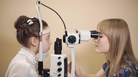 yarık : Female oculist checking eyes of young girl at the office. Ophthalmologist using slit lamp for examination. Stok Video