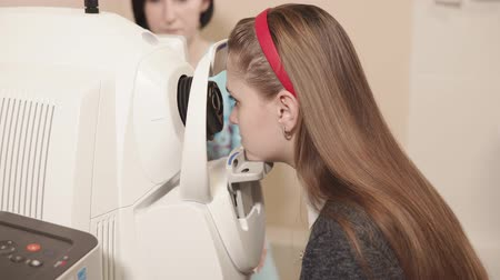 examinar : Side view shot of young girl having her eyes examed on eye tomography machine in hospital. Ophthalmologists office.