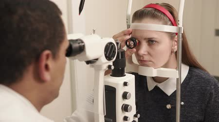 фиксация : the oculist doctor works in a private clinic, the man uses an apparatus for biomicroscopy of the eye to check the sight of an adult teenager